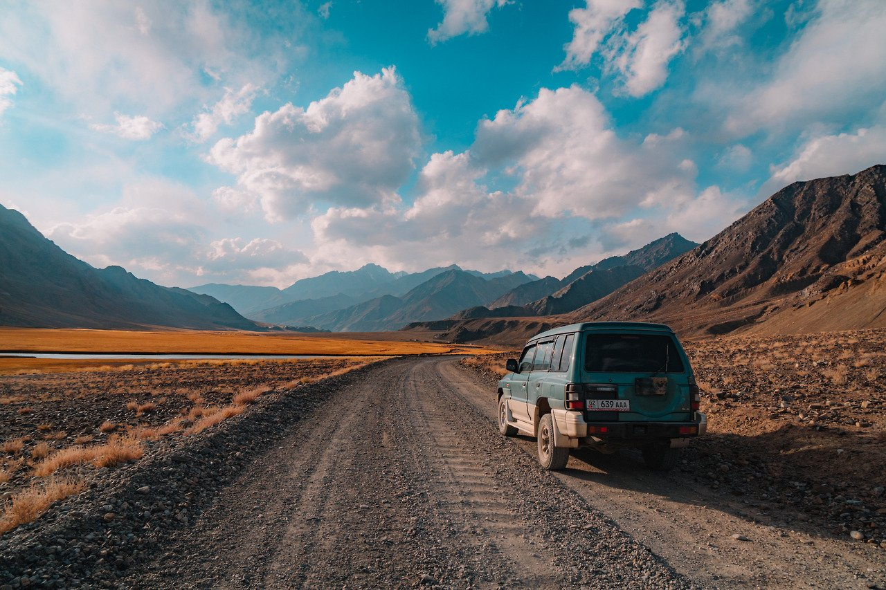 A jeep parked along a dusty road on the Pamir Highway.