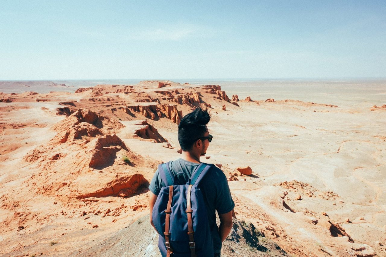 A person looking at the Flaming Cliff in the Gobi Desert, Mongolia.