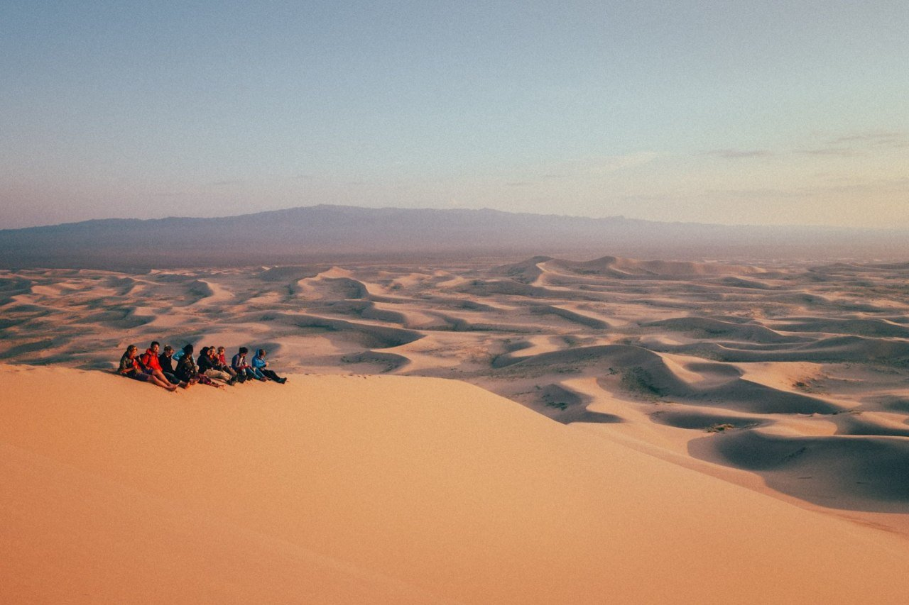 People sitting on a sand dune while watchin sunset in the Gobi desert, Mongolia