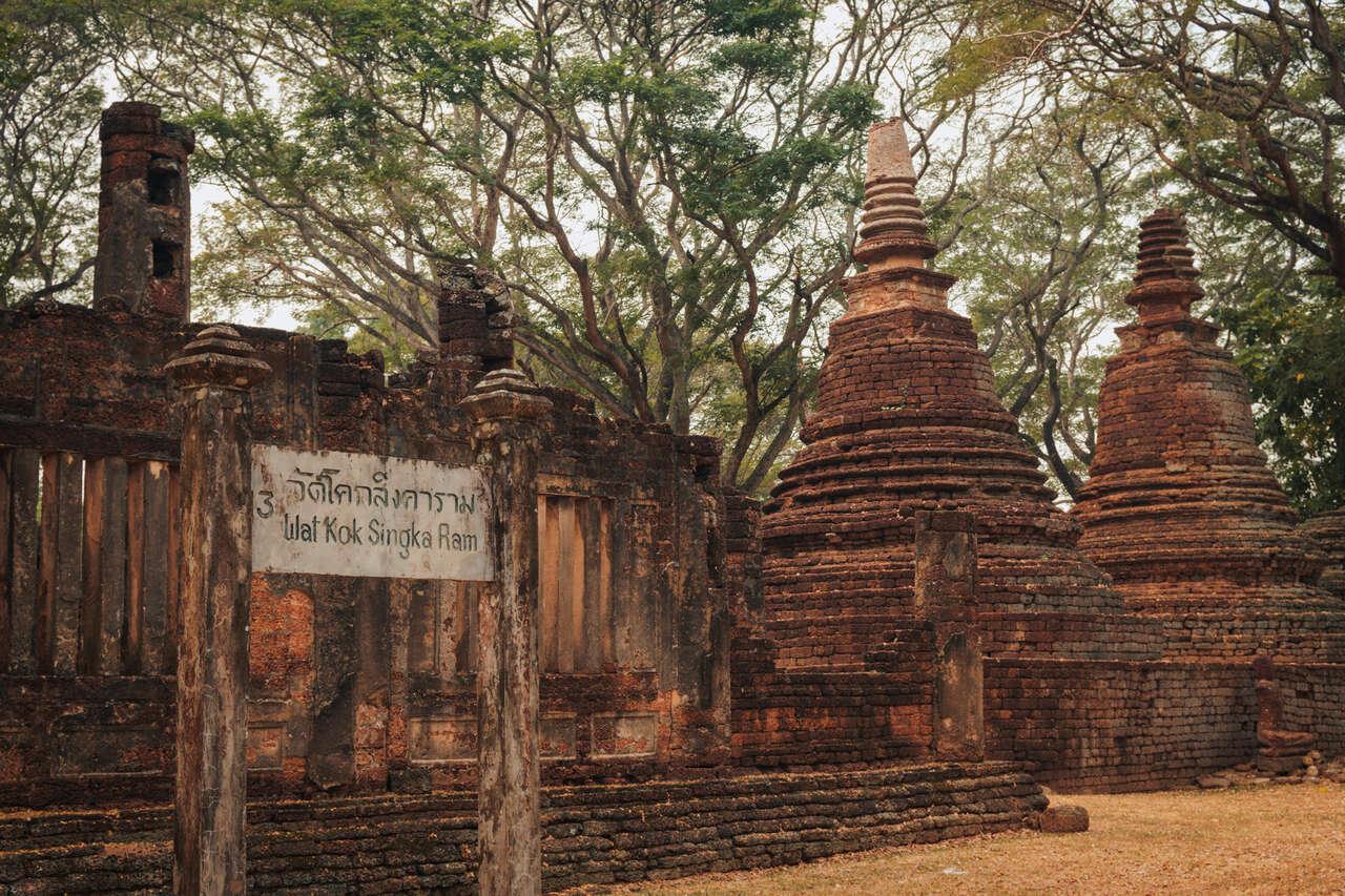 Wat Khok Singkharam and its sign in Si Satchanalai, Thailand
