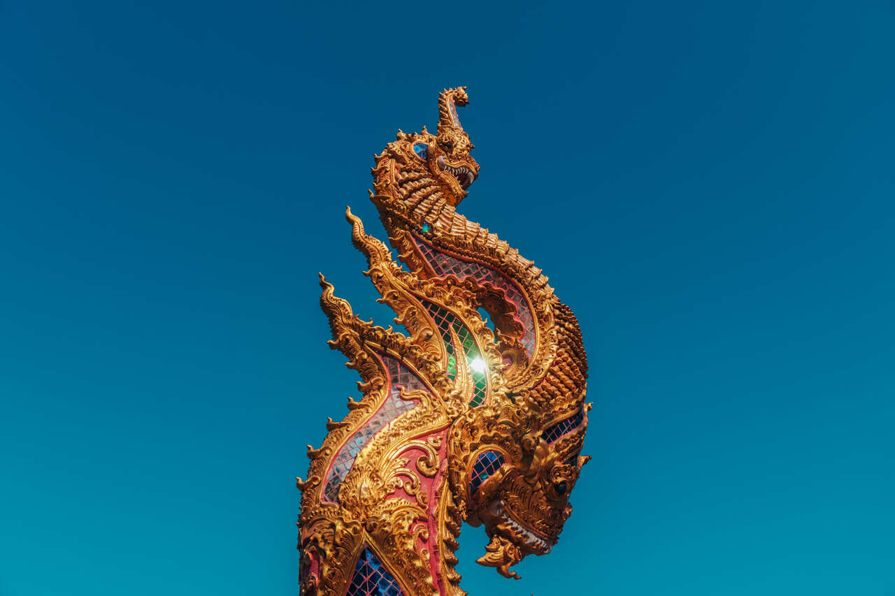 The richly decorated naga tail at the entrance of Wat Kaew Don Tao Suchadaram in Lampang, Thailand.