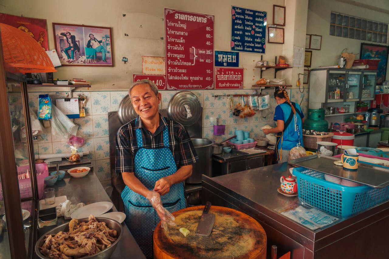 The lovely owner making Hainanese chicken rice at Khao Mun Kai Ha Yak in Lampang, Thailand.