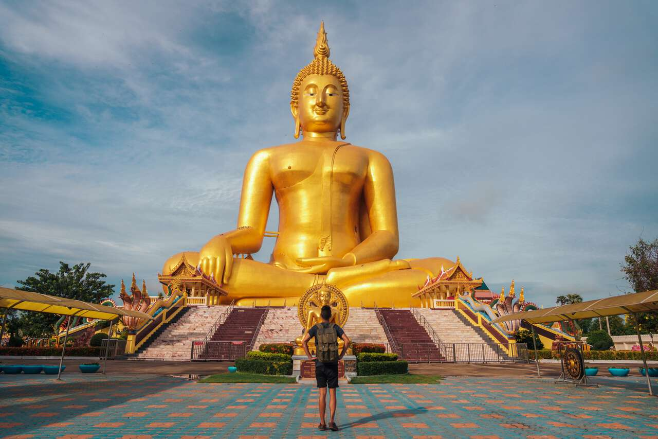 A traveler standing in front of The Great Buddha of Thailand in Ang Thong