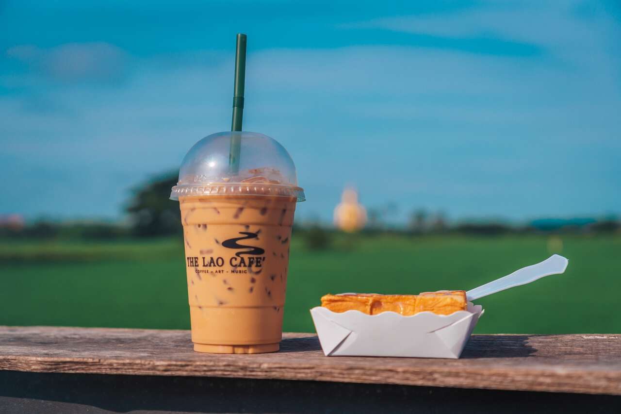 Iced Lao Coffee on a wooden table by a rice field with the Great Buddha of Thailand in the background.