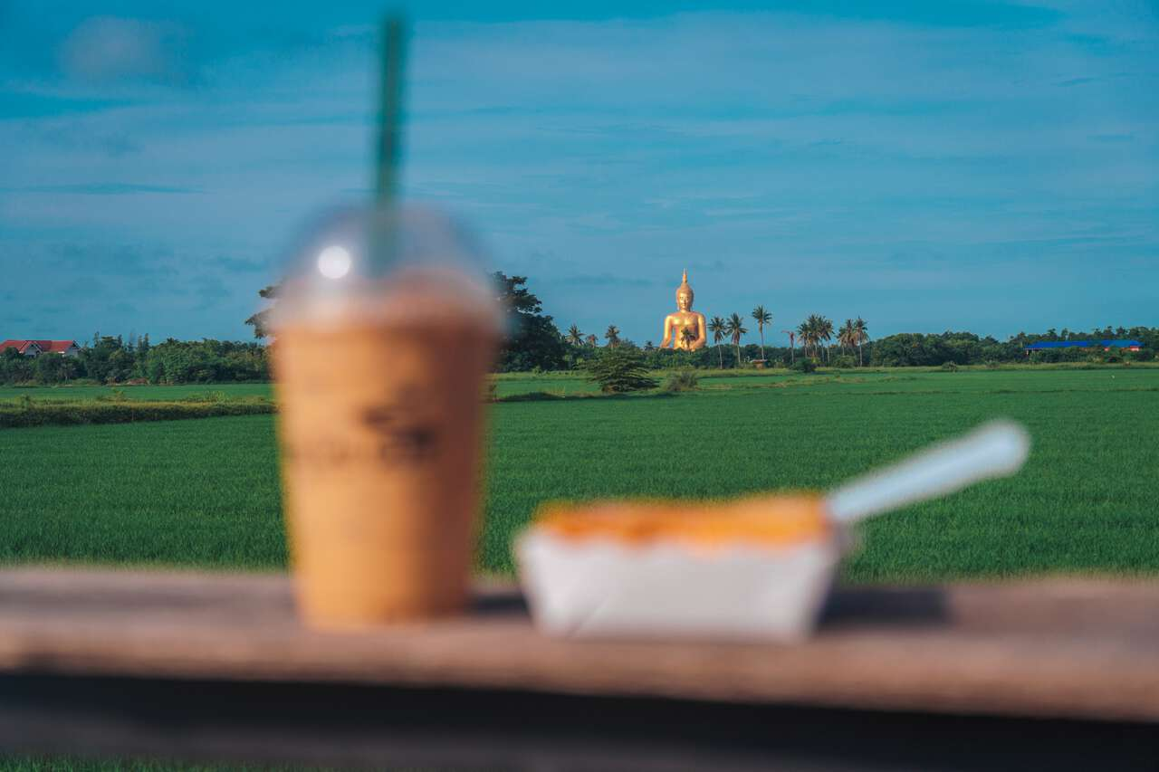 The view from the Lao Cafe by a rice field with the Great Buddha of Thailand in the background.